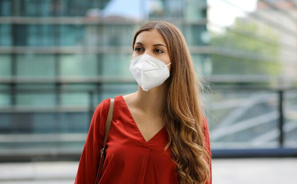Sense of bewilderment. Young woman in empty city street wearing protective mask. Girl with face mask feeling alone during a pandemic.