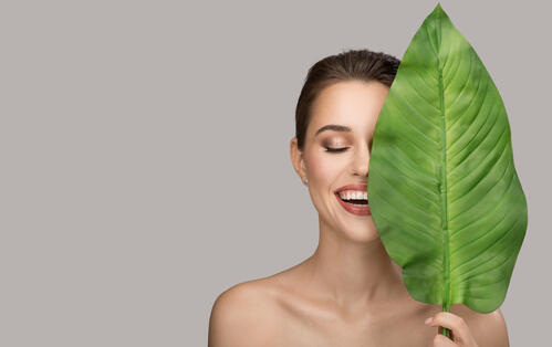 Portrait of woman and green leaf. Organic beauty. Gray background