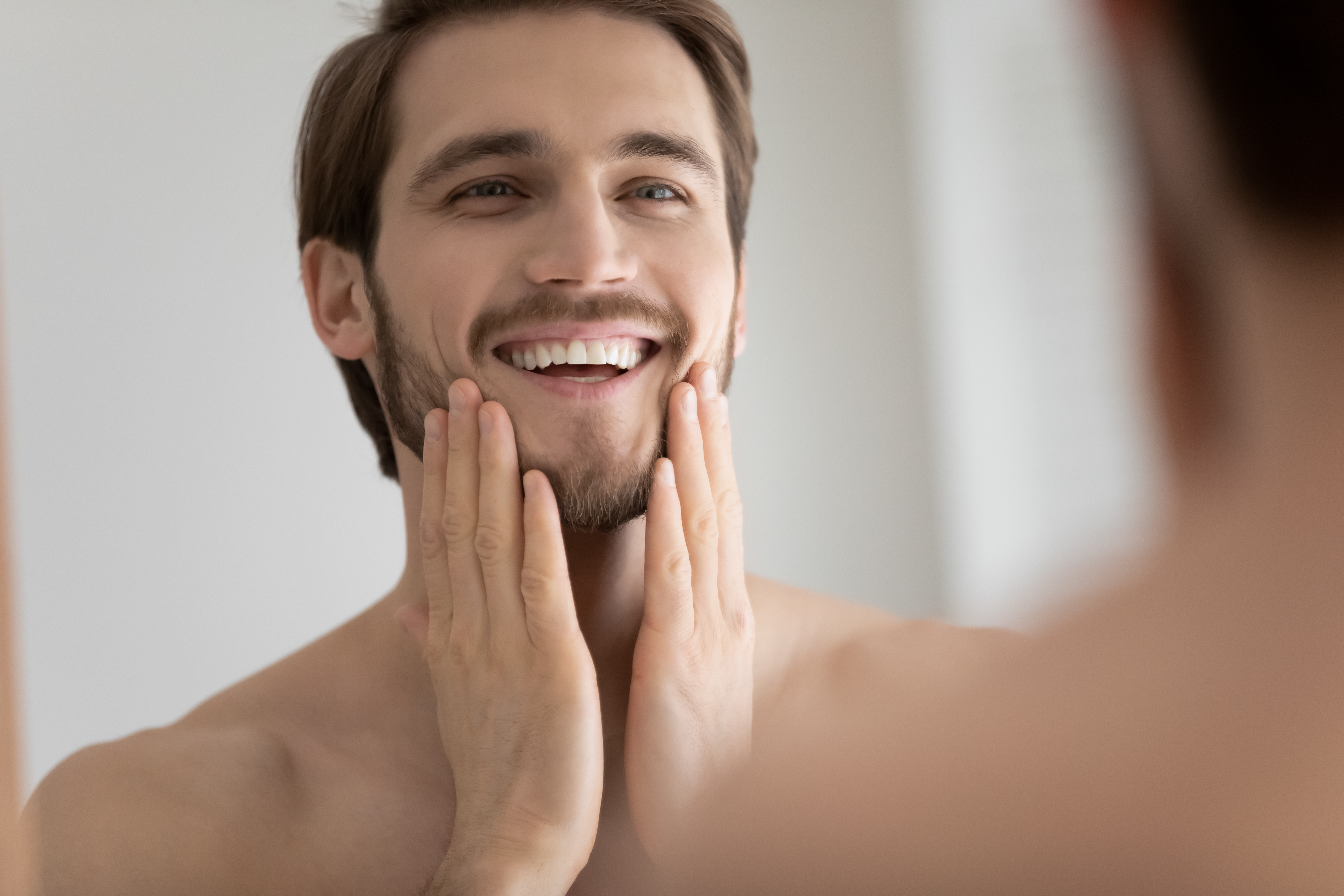 Smiling young Caucasian man look in mirror in bathroom touch healthy face skin after treatment or procedure, happy millennial male satisfied with beard or bristle after shaving, body hygiene concept