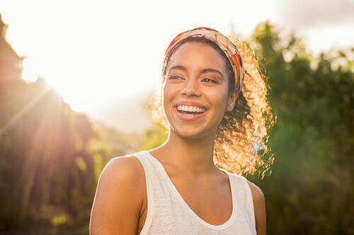 Young black woman smiling at sunset