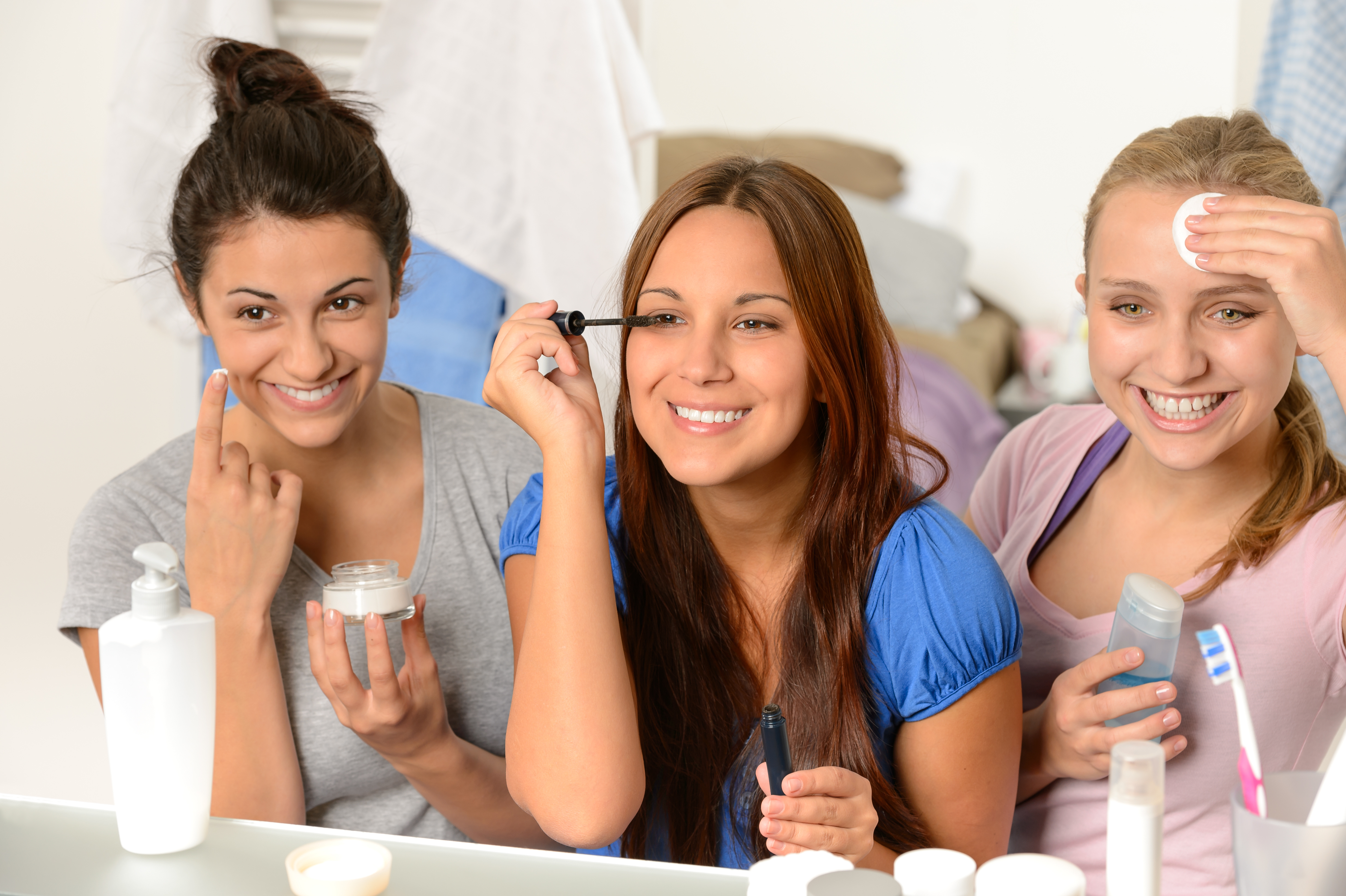 3 teen girls applying skin care products