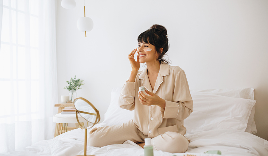 Smiling woman applying face cream sitting on bed.jpg
