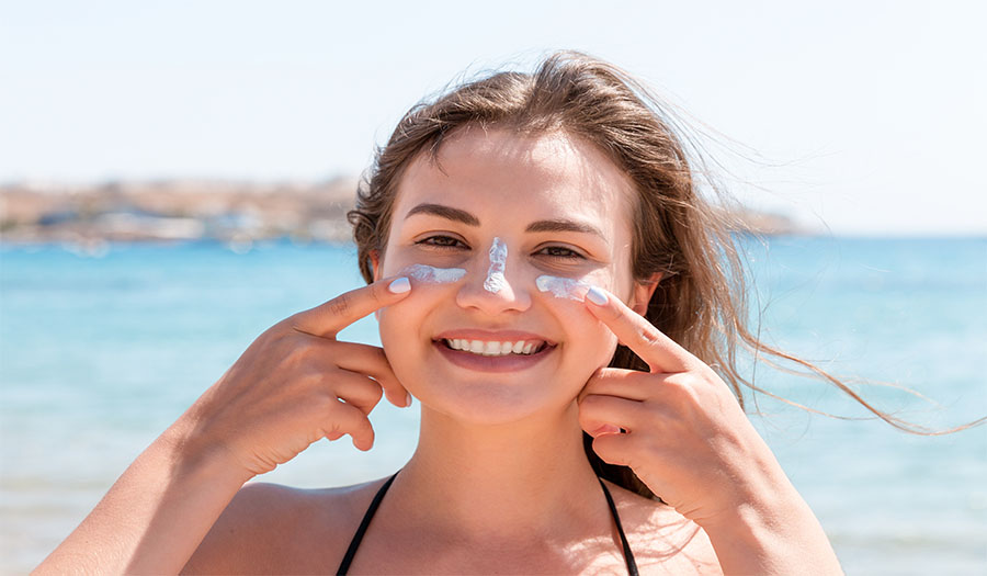 Tanned woman protects her face with sun cream from sunburn at the beach