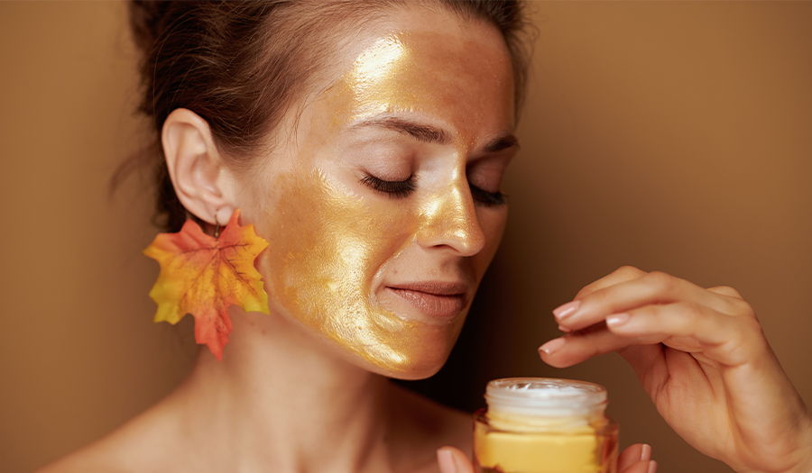 young woman with golden mask using cosmetic product