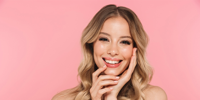 Blonde woman smiling on a pink backdrop