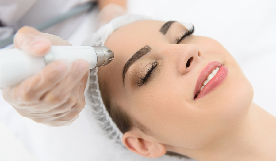 Cheerful woman getting laser therapy at spa salon
