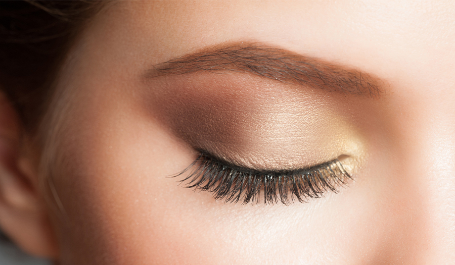 Close of up a womans eyelids with a touch of yellow makeup