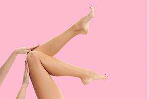 Womans legs infront of pink background