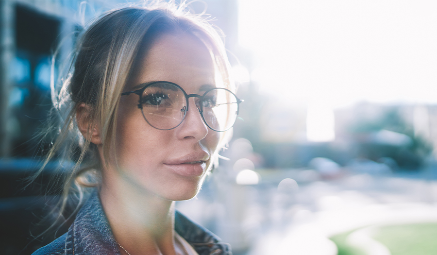 Young blonde woman in glasses in front of blurred city sunset